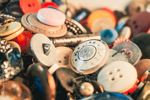 Fotografering Selective focus shot of colorful buttons of different sizes and sewing materials