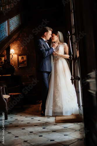 Foto bride and groom in the sunlight at the glass door