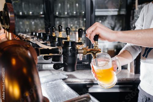 Canvastavla Close-up of the bartender filling a mug of light beer