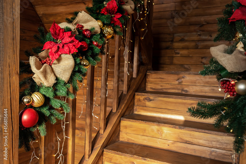 Valokuvatapetti Detail house wooden staricase handrails railings decorated with artificial holly poinsettia flower, burlap bow, christmas tree and golden lights garland