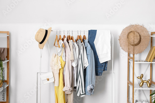 Obraz na plátně Rack with stylish clothes and accessories near light wall