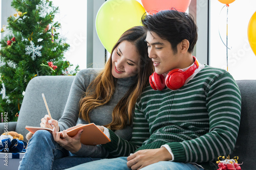 Canvastavla Young Asian man with red earphone relax sit together with lovely girlfriend who