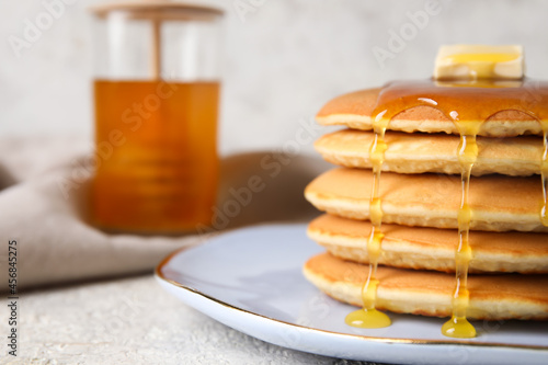 Fotografie, Obraz Plate of tasty pancakes with honey and butter on light background, closeup