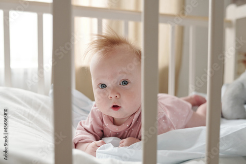 Fotografie, Obraz Cute infant girl in pink clothes looking at you while crowling in her cradle