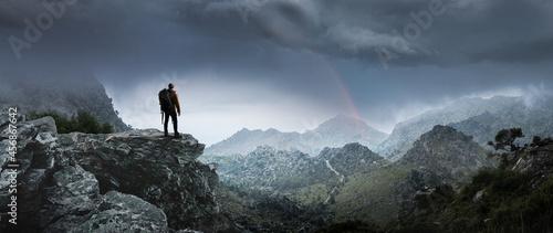 Obraz na plátně Wanderer in Berglandschaft schaut auf einen Regenbogen