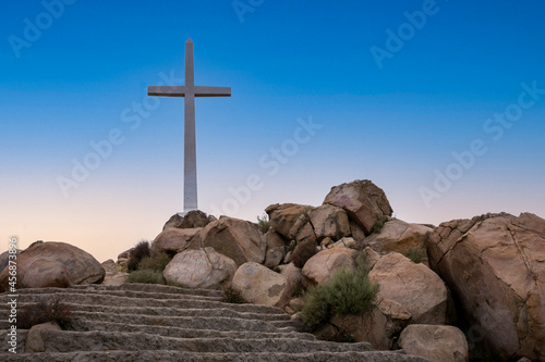 Canvastavla Low angle shot of cross on the top of stairs among stones against clear sky