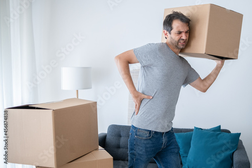 Fotografie, Obraz Man lifting boxes and moving into new house suffers backache