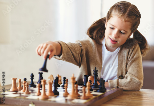 Cute little girl playing chess while spending leisure time at home during during Fotobehang