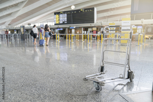 Cuadros en Lienzo Modern airport with tourists and a metal handcart in the foreground