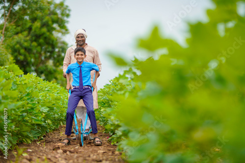 Young indian farmer with his son at green agriculture field. Fototapeta