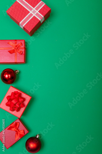 Composition of presents with bauble and copy space on green background