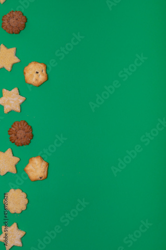 Composition of christmas cookies and copy space on green background