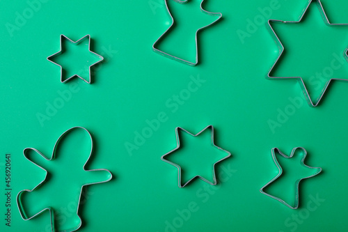 Composition of star and angel ginger man cookie cutters on green background