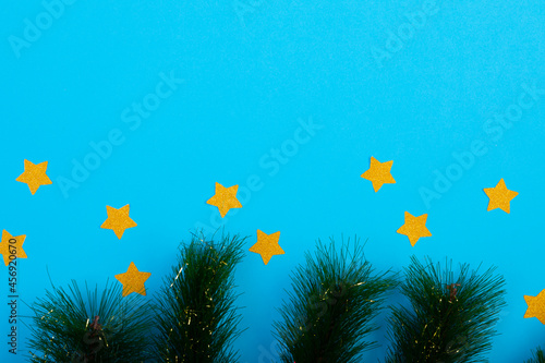 Composition of fir tree branches with stars and copy space on blue background