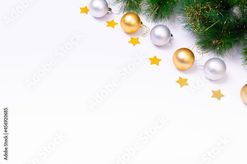 Composition of fir tree branches with baubles, stars and copy space on white background
