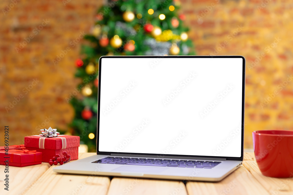 Leinwandbild Motiv - wavebreak3 : Composition of laptop with copy space on wooden table with christmas tree in background