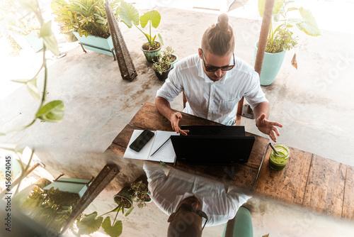 Obraz na plátně Mężczyzna pracujący przy laptopie z telefonem, praca zdalna podczas podróży, cyfrowy nomada w kawiarni