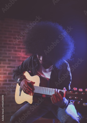 African american male musician playing guitar sitting on a table against brick wall