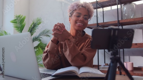 Fotografie, Obraz Young friendly African American woman is recording her video blog