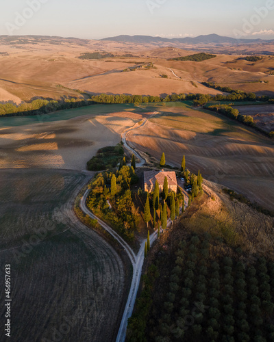 Fotografie, Obraz Aerial view of a small house on hilltop surrounded with vineyard at sunset in Val d'Orcia, Tuscany, Italy