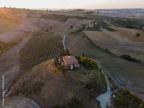 Fototapeta premium Aerial view of a small house on hilltop surrounded with vineyard at sunset in Val d'Orcia, Tuscany, Italy.