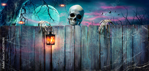 Slika na platnu Halloween - Skeleton Holding Lantern On Wooden Banner In Night