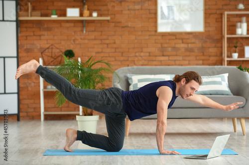 Fototapeta premium Young man practicing yoga at home