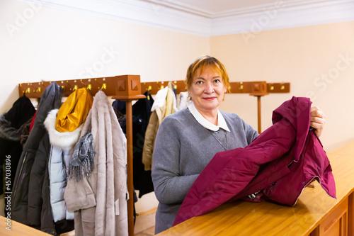 Obraz na plátně Female cloakroom attendant gives out clothes at the cinema