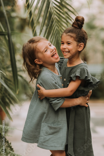 Obraz na plátně Portrait of two charming smiling girls belonging to different races surrounded by tropical leaves