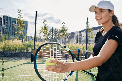 Fototapeta premium Positive female tennis player with tennis ball and racket, standing on court outdoors while practicing hitting