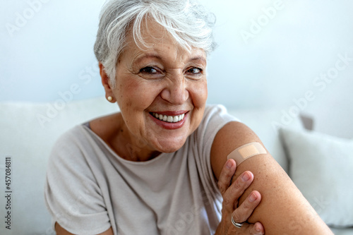 Billede på lærred Proud mature woman smile after vaccination with bandage on arm