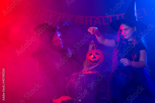 Wallpaper Mural Two halloween witches making a potion and conjure in halloween night