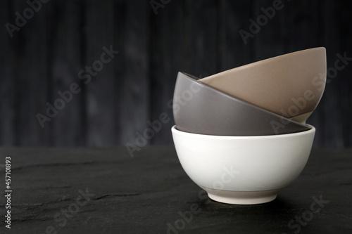 Billede på lærred Stylish empty ceramic bowls on black table, space for text