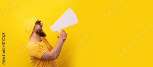 Vászonkép man screaming into  megaphone over yellow background, panoramic layout