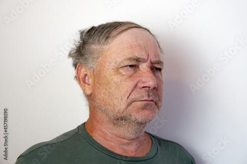 Fotografie, Obraz portrait of a disgruntled elderly frowning man on a light background