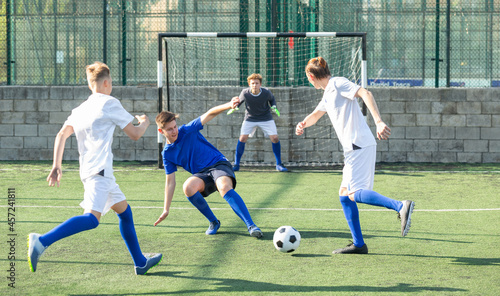 Fototapeta premium Game moments of football match between two teams of teenagers in white and blue shirts
