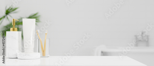 Photographie White tabletop with toothbrush, shampoo bottle, body lotion tube over bright whi
