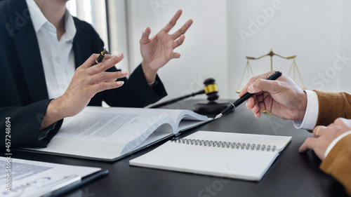 Fotografie, Obraz law,libra scale and hammer on the table, 2 lawyers are discussing about legal provision, law matters determination, body language