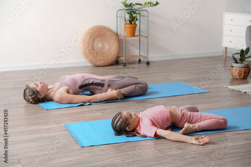 Little girl with her mother practicing yoga at home