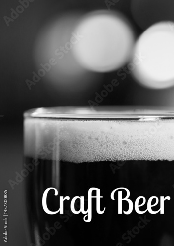 Craft beer text over close up of beer class against black background