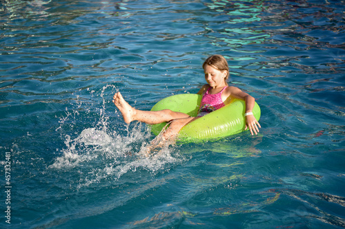 the girl swims in the evening on a large circle and splashes fly
