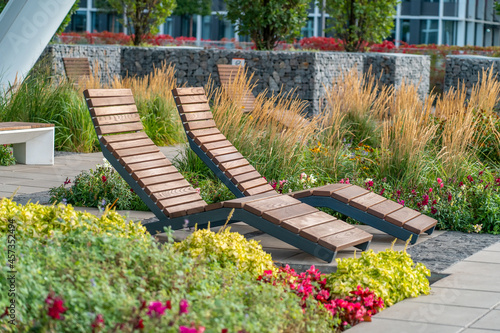 Fotografering Two empty brown wooden deck chairs or chaise longues on tile among decorative grass and flowers in recreation area