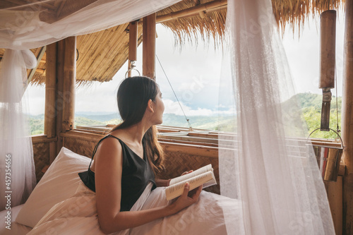Young asian woman resting and reading a book on the bed in thatched hut among th Fototapet