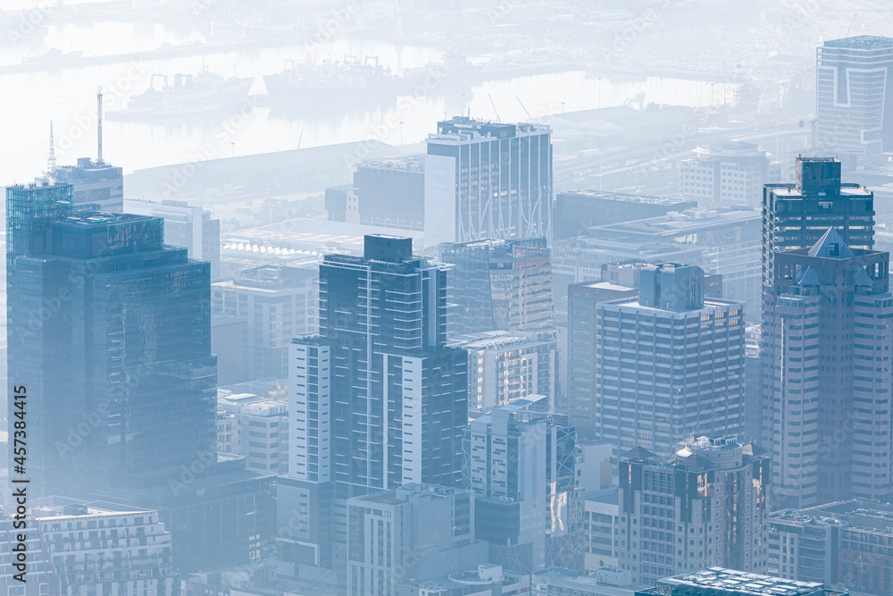 General view of cityscape with multiple modern buildings and cranes in the foggy morning