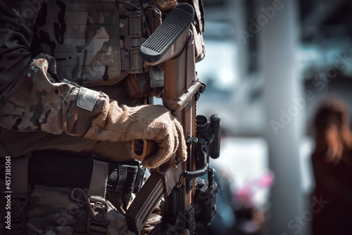 Fototapeta Close-up of a soldier holding modern rifle