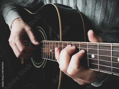 man's hands playing acoustic guitar closeup