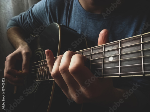 close up of man's hands playing acoustic guitar