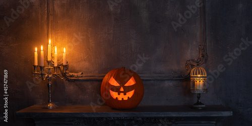 Canvas Print Scary laughing pumpkin and old skull on ancient gothic fireplace