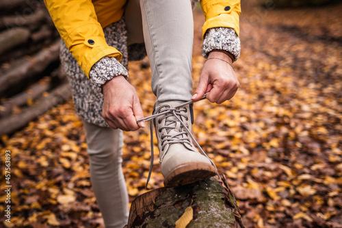 Fotografie, Obraz Woman tying shoelace on her hiking boot