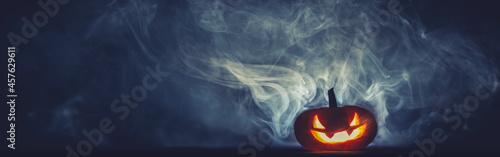 Obraz na płótnie Spooky carved Jack o Lantern glowing red in thick smoke at night